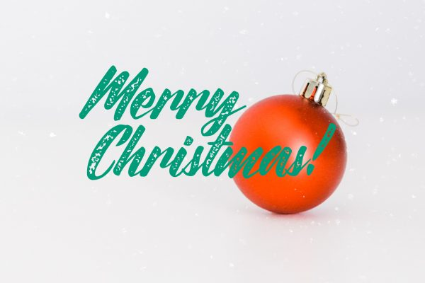Red ornament and green text saying Merry Christmas